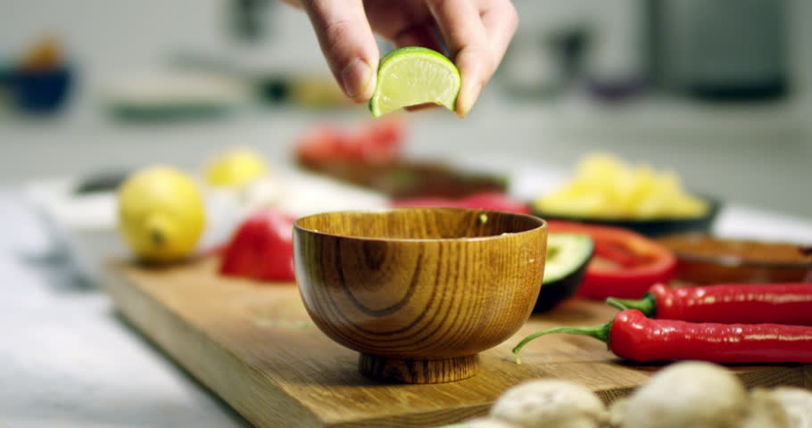 Squeezing a lime in slow motion above wooden bowl. Cutting fresh vegetables on a wooden bench in a modern kitchen with shallow focus and blurred background. Strong and vivid colors.