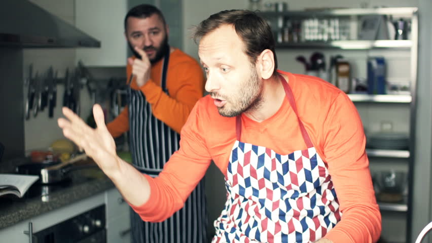 Two male friends fighting, arguing while cooking in kitchen
