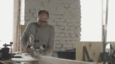Adult locksmith in glasses cutting wooden board by plunge router. Treatment. Sawdust. Manufacturer.