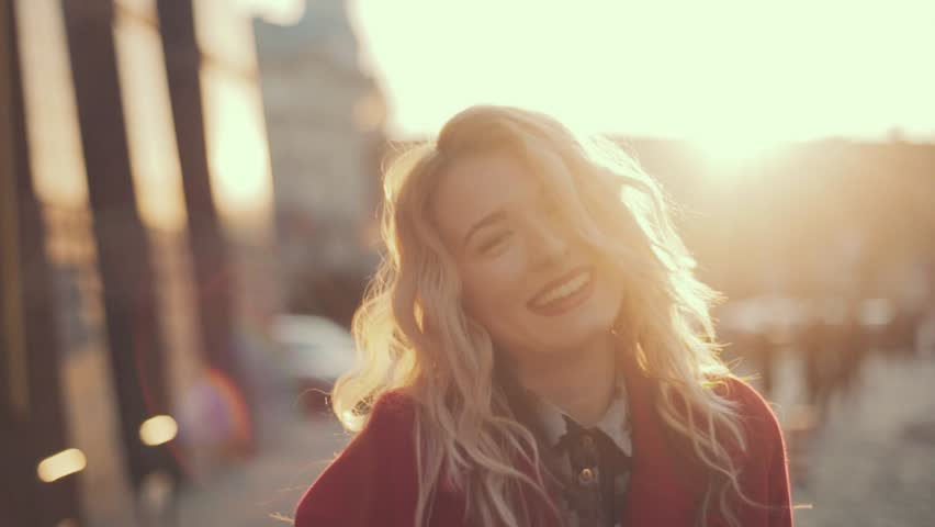 Attractive girl in a red coat with red lips goes down the street in a city, sun is shining, than turns to camera and smiles | Shutterstock HD Video #15557680