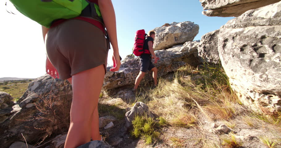 Hiking man helping his girl friend climbing a rock while travelling together in sunny outdoors | Shutterstock HD Video #15558214
