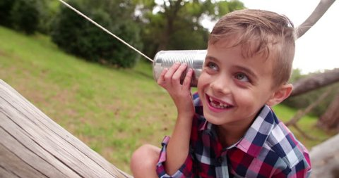 Mischievous Boy listening on tin can phone in his hands, concept for telephone or mobile communication.