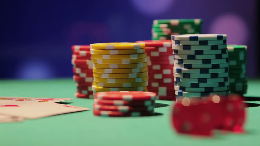 Rack focus shot of pile of poker chips and dice on table, casino background | Shutterstock HD Video #15582160