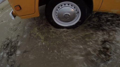 A closeup of a 1977 volkswagen bus' tire is seen while driving on the beach through the ocean.