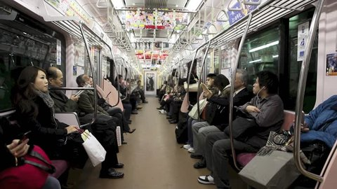 Subway interior with passengers arriving at station, Tokyo, Japan, December 2009