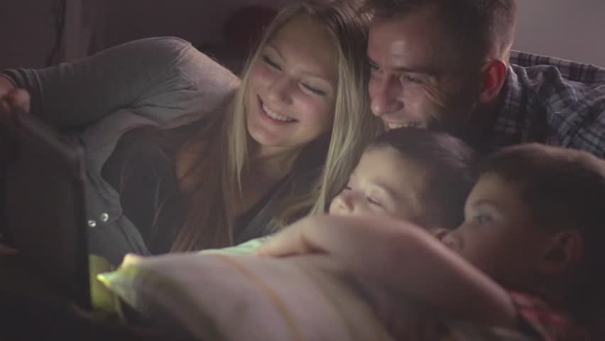 Happy family- Father, mother and Two kids lying down on the sofa and using tablet pc at night. Family watching movie on tablet computer in a dark room. HD 1080p, slow motion 240 fps, high speed camera | Shutterstock HD Video #15640990
