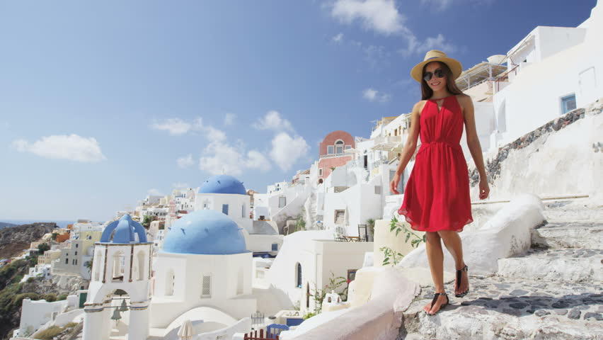 Tourist woman on travel walking on steps in Oia, Santorini, Greek Islands, Greece, Europe. Asian on travel enjoying vacation visiting famous tourist attraction destination, blue Domes on church. | Shutterstock HD Video #15647017