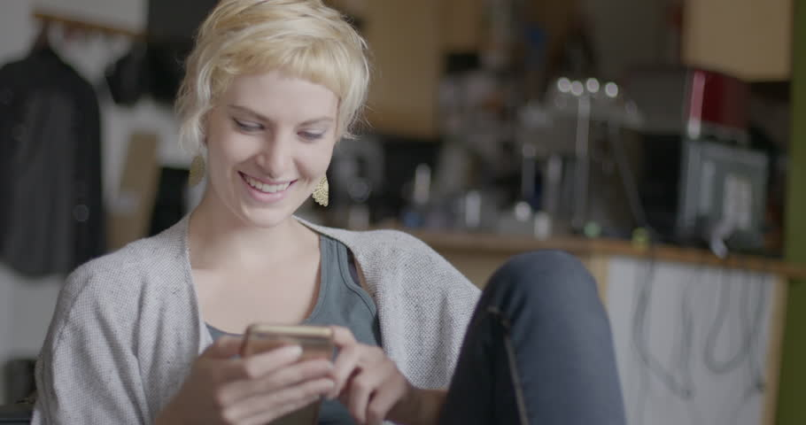 Attractive young woman laughs while using a smart phone in urban loft location. Medium close up, hand-held camera recorded at 60fps.