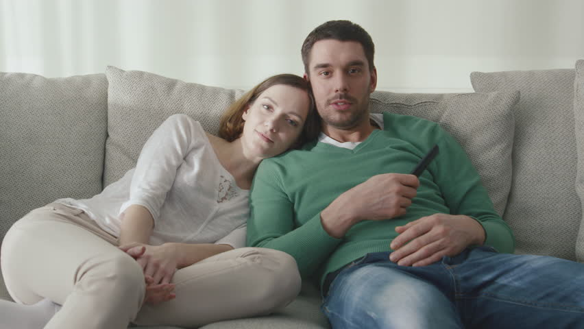 Couple is sitting on the couch at home and watching tv. Shot on RED Cinema Camera in 4K (UHD).