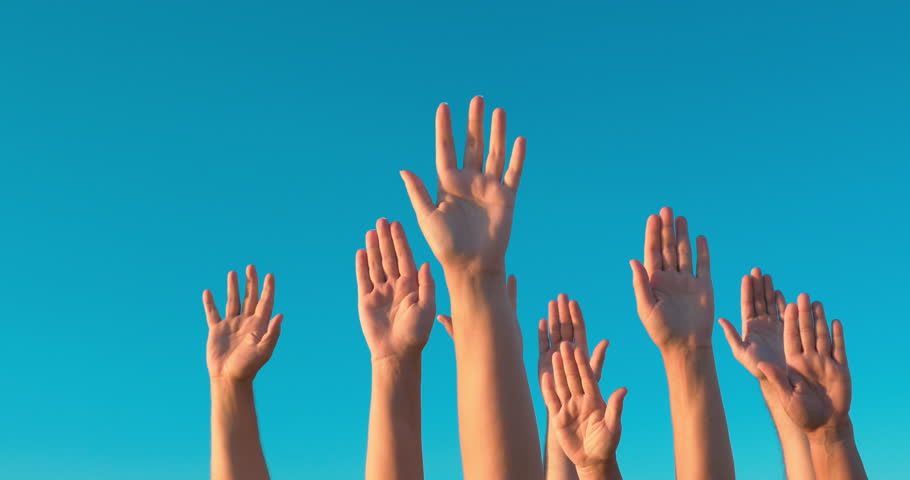 People rasing hands on blue sky background. Voting, democracy or volunteering concept