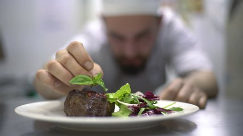 Chef is finishing meal teasty beef steak with salad for guest of restaurant. Final touch basil leaf