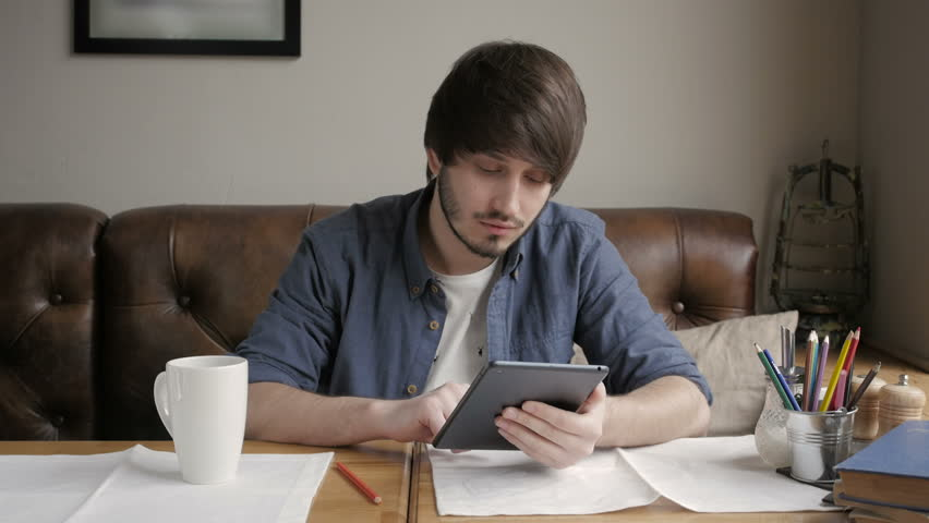 Young Fashion Man  Hipster Drinking  Coffee in the City Cafe During lunch time and Working on Tablet Computer | Shutterstock HD Video #15744040