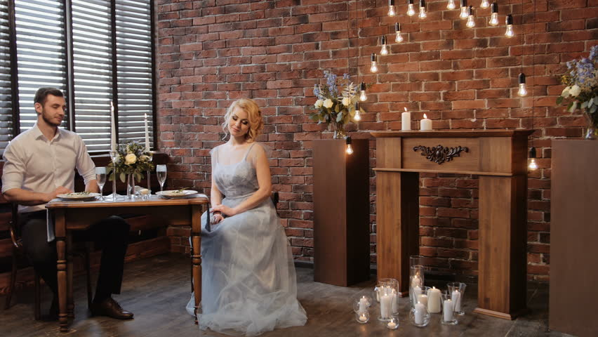 Wedding. Decor. Serving. Artwork. Pan shot of bride's and groom in a suit sitting at served table on the background of a brick and shutters #15774520