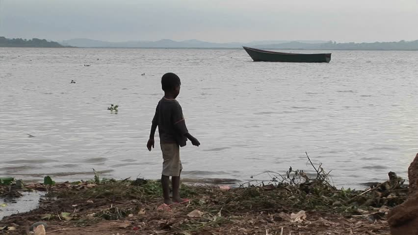 LAKE VICTORIA, UGANDA - CIRCA 2009: A young boy plays along shore circa 2009 in Lake Victoria.