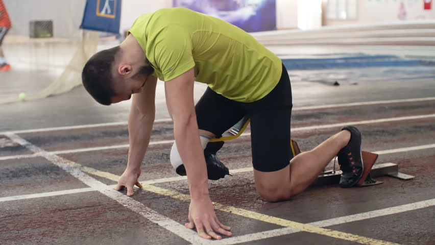 Slow motion shot of determined athlete with prosthetic leg starting from blocks on track