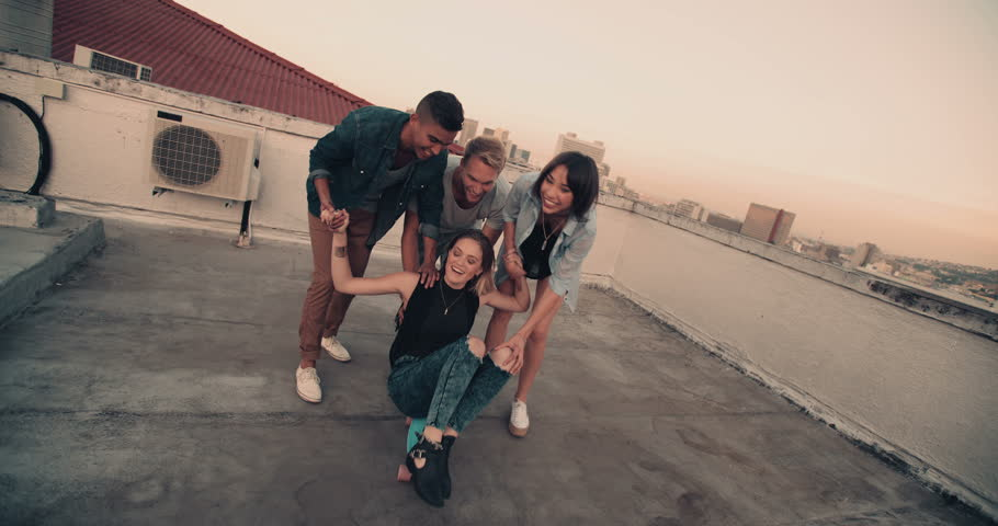 Girl is being pushed on skateboard on the rooftop by a group of friends | Shutterstock Video #15814591