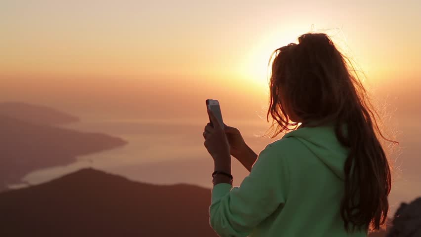 Young Attractive Woman Watching Sunset or Sunrise Over Bay from Top of the Mountain, Girl Takes Panorama Photos On Phone.Hair in the Wind. Handheld Atmospheric Shot. Crimea, Ukraine.