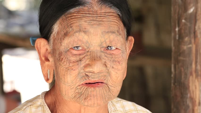 MRAUK-U, MYANMAR - JANUARY 27, 2016: The portrait of Chin woman with spider tattoo. Chin people, also known as the Kukis are a number of Tibeto Burman tribal people. | Shutterstock HD Video #15828010