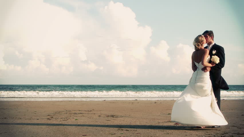 Attractive newlywed couple kissing on the beach in slow motion in cinemagraph