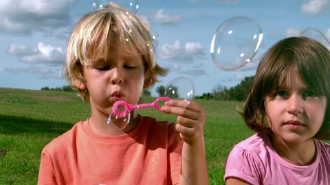 Small boy blowing bubbles with a girl in cinemagraph style