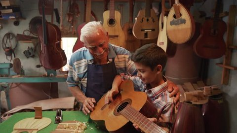 Generation gap, family business, old and young people showing love for music. Boy and senior man, happy kid and elderly person, grandpa teaching child how to play guitar in workshop