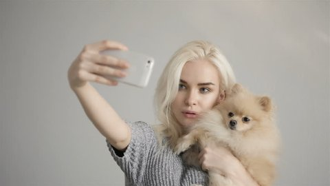 Beautiful Blonde Woman Making Selfie With Her Spitz Isolated On Grey