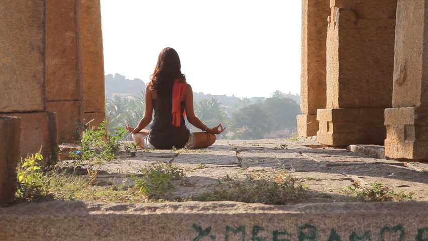 young woman mediating in nature