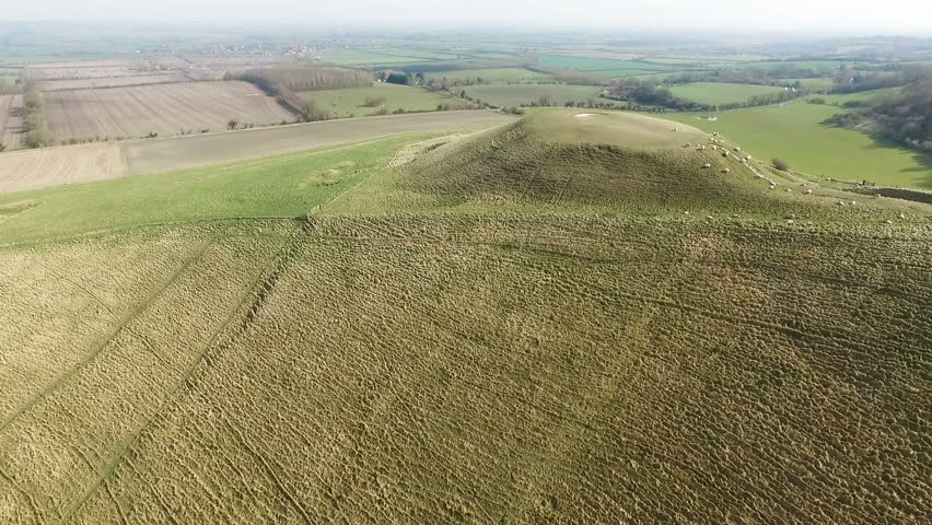Aerial view looking across a hillside with a large iron age castle mound next to Uffington White horse