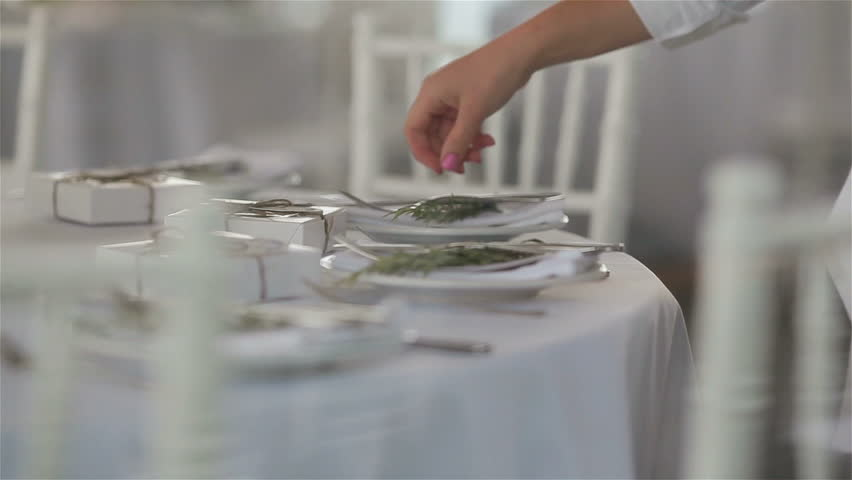 Close up macro of table in a restaurant elegantly served for lunch or dinner. Cutlery – tableware and silverware. Water hands carefully wiping fork and knife