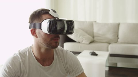 Man Wearing VR Headset at Living Room. Using Gestures with Hands.Shot on RED Cinema Camera.