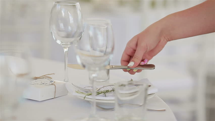 Catering job profession planner. Waiter hands arranging table setting with place card for wedding guests in a restaurant