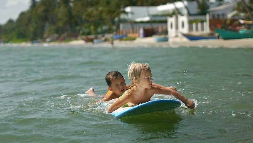 Happy smiling adorable little children enjoying blue sea surfboarding on surfboard on summer vacation in slow motion | Shutterstock HD Video #15940090