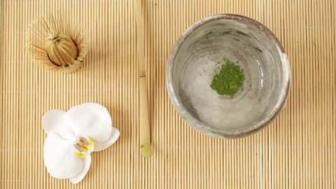 Male hand preparing Matcha green tea on Tatami mat