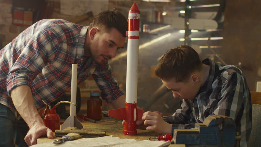 Father and son are modeling a toy rocket in a garage at home. Shot on RED Cinema Camera in 4K (UHD). | Shutterstock HD Video #15989293