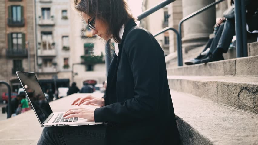 Side view of young attractive female student sitting on the stairs of University and using modern laptop, businesswoman typing on computer keyboard while working on a break outdoors, slow motion | Shutterstock HD Video #16045822