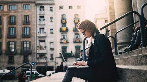 Close-up of young attractive businesswoman using laptop on a break outdoors, beautiful female student sitting on the stairs of University, slow motion
