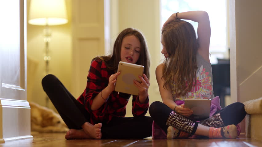 Two friends sitting together in the hallway using their tablets | Shutterstock HD Video #16070620