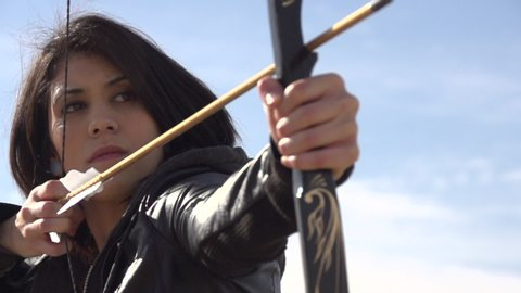 A female archer shooting targets with her bow and arrow. - Super Slow Motion - Model Released - filmed at 240 fps
