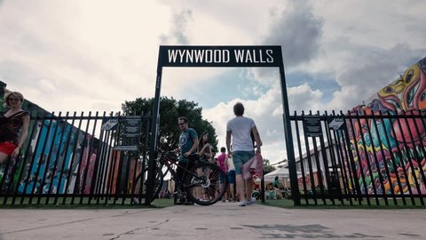 MIAMI, USA - MARCH 19, 2016: (Time lapse) Wynwood Wall entrance with people. The Wynwood Art District Association was founded in early 2003 by a group of art dealers, artists and curators.