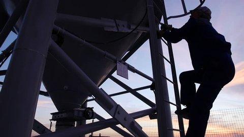Technician climbing an oil storage tank at sunset