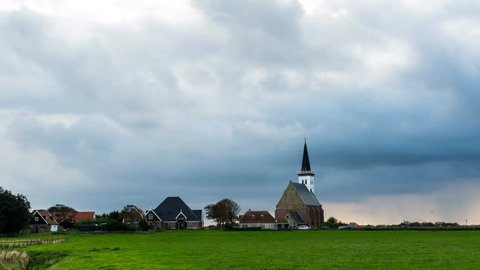 Sunset and clouds at the small, white church of Den Hoorn  on the island of Texel, The Netherlands.