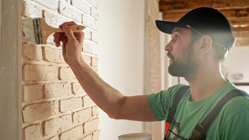 Renovation: man painting a wall, enjoying the work. Slow motion