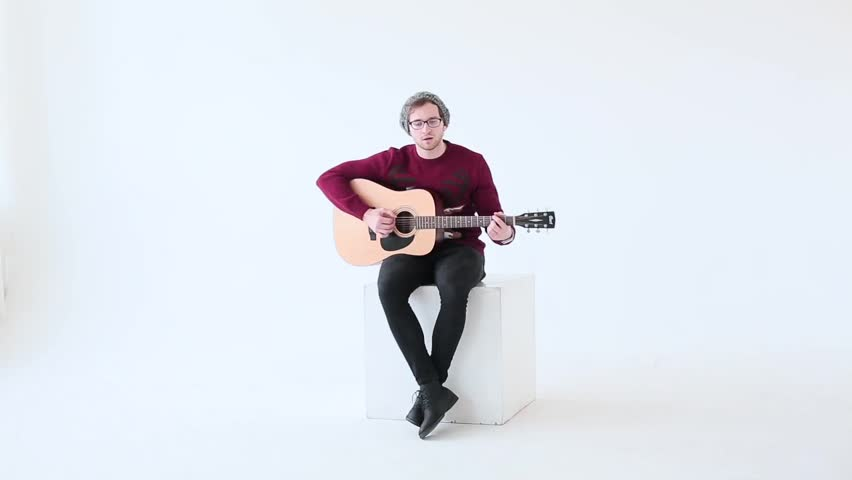Man playing an acoustic guitar on the white studio background.