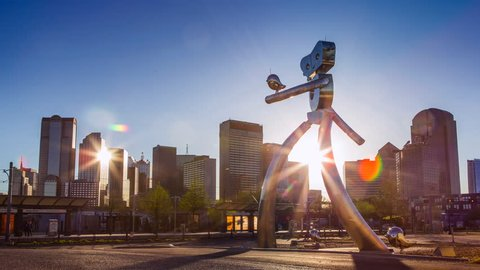 Dallas, Texas/USA - 03/31/2016: Dallas Sunset Time Lapse: The Travelling Man is a steel sculpture located at the Deep Ellum Station in Dallas. Sculptures by Brad Oldham and Brandon Oldenburg.