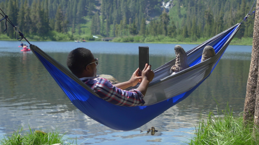a man resting in a hammock and using a tablet mobile device near a mountain lake girl riding canoe in the river  having fun outdoors as paddling a      rh   shutterstock