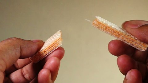 Hand holds wafer of cheese and breaks it. Slow motion