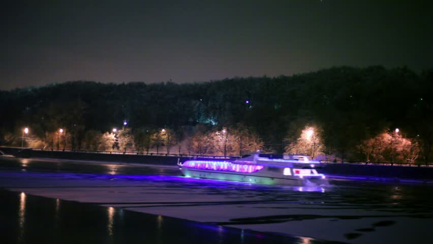 Motor ship decorated with garlands, floats down the river at winter night