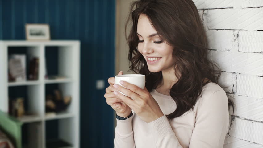 Happy girl drinking coffee and relaxing in cafe, smiling and looking at camera.  | Shutterstock HD Video #16256659