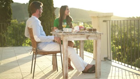 4k footage, young couple having breakfast outside on huge balcony on sunny morning in rural landscape