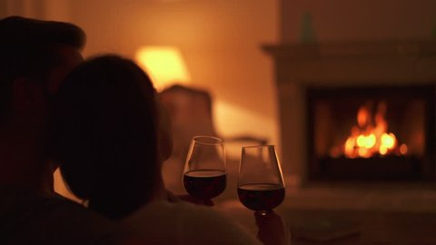 4k footage, closeup back view young couple relaxing on sofa at home in front of fireplace in the evening with red wine